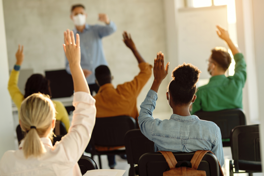 Students raising hands in classroom setting